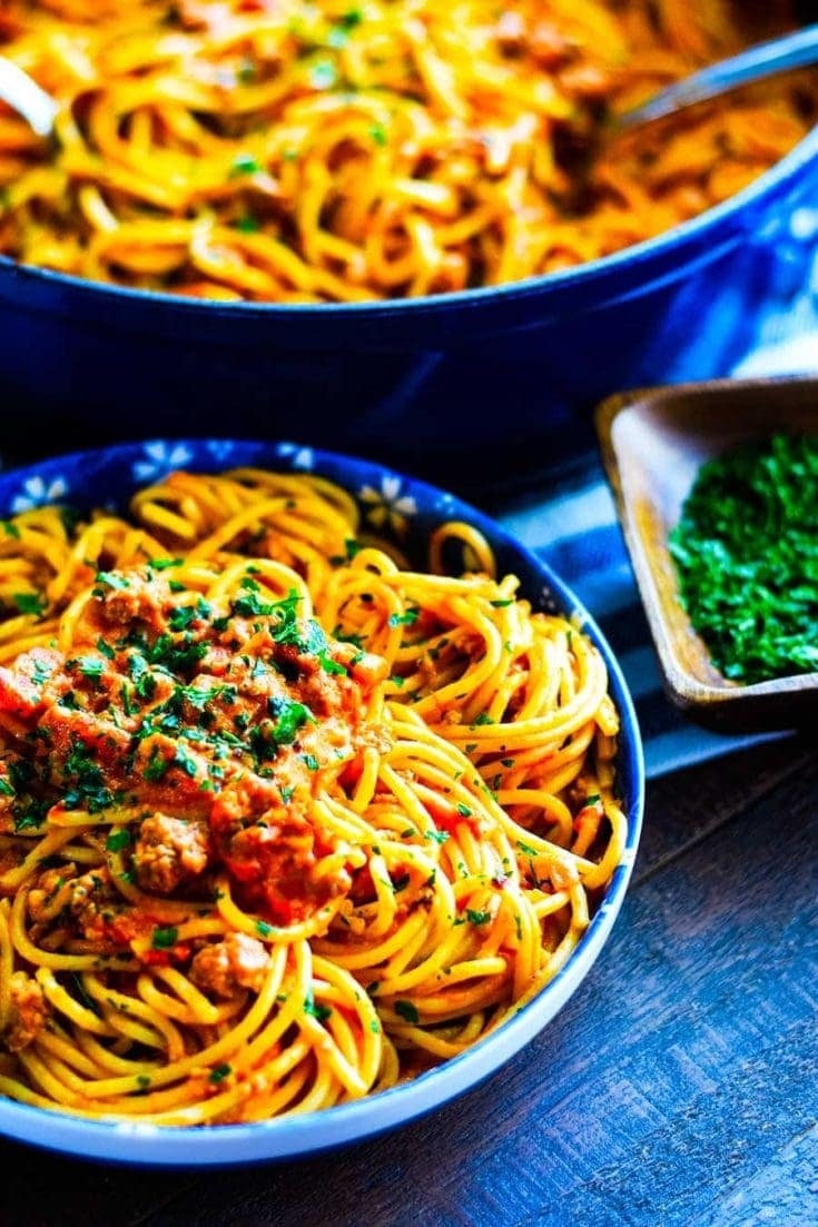 Sausage Spaghetti with a creamy tomato sauce in blue bowl with white flowers. Set on a wooden table and garnished with parsley.