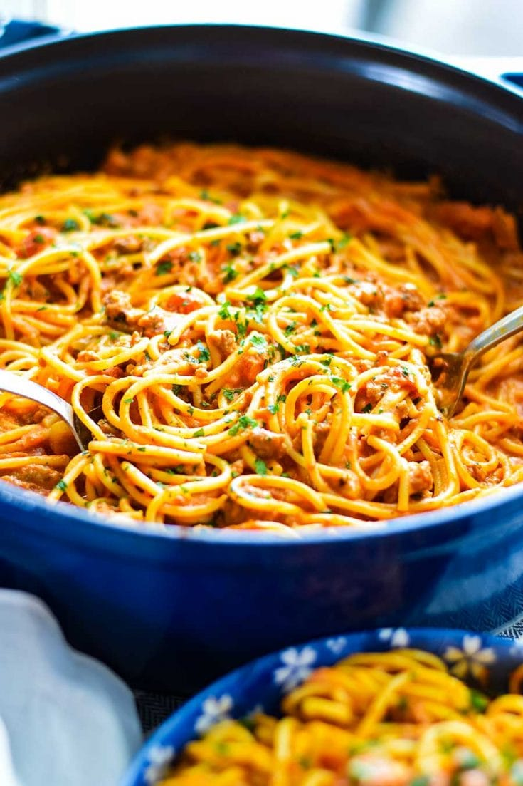 Creamy Spicy Spaghetti with Sausage topped with parsley in a blue casserole skillet being served with tongs.