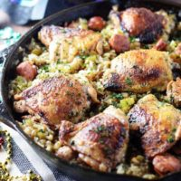 Chicken thighs with cajun style dirty rice in a cast iron skillet