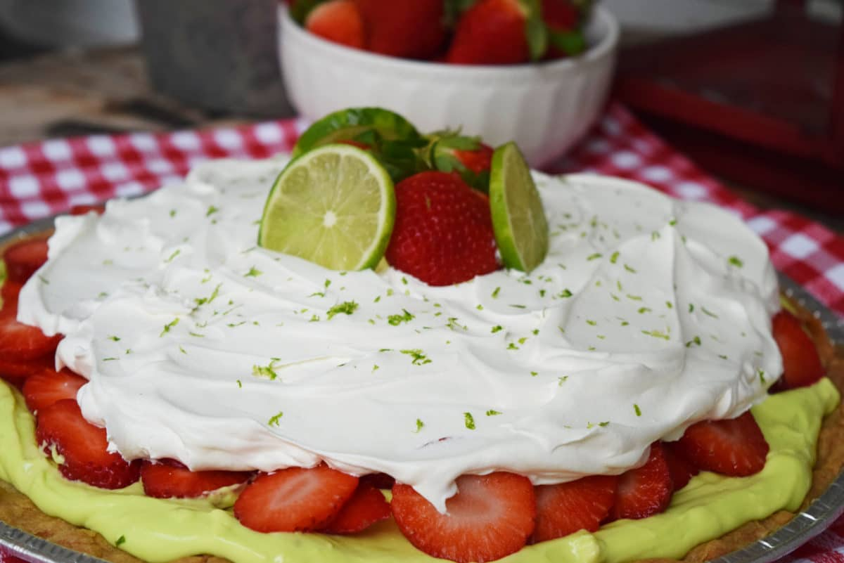 Strawberry Margarita Pizza topped with Whipped Cream and garnished with limes and strawberries
