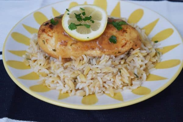 Lemon and Garlic Chicken on bed of rice pilaf garnished with lemon and parsley.