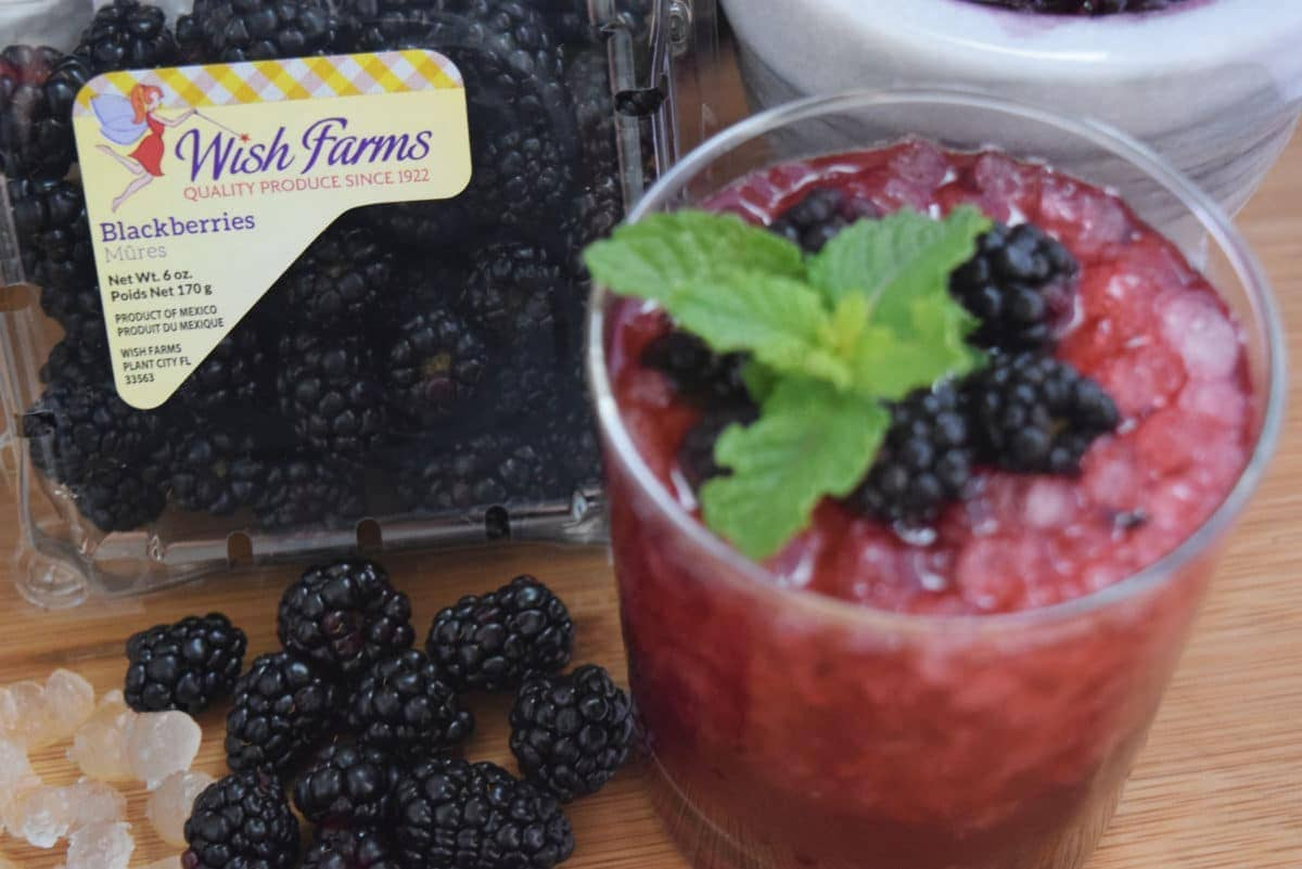 Blackberry Bramble Wish Cocktail in a glass with crushed ice on a wooden tray with wish farms blackberry container in the background.