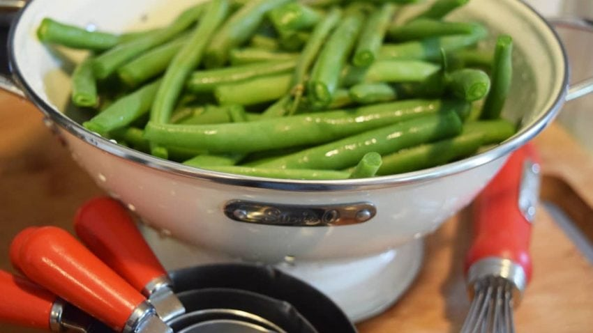 Fresh Snapped Green Beans rinsed with water in a while colander.