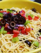 a closeup of a bowl of shelly's pasta salad comprised of spaghetti noodles, black olives, red onion, celery, and red bell pepper
