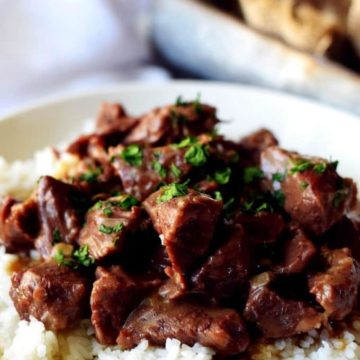 A white plate filled with white rice and this instant pot beef tips recipe aka pressure cooker beef tips garnished with chopped parsley