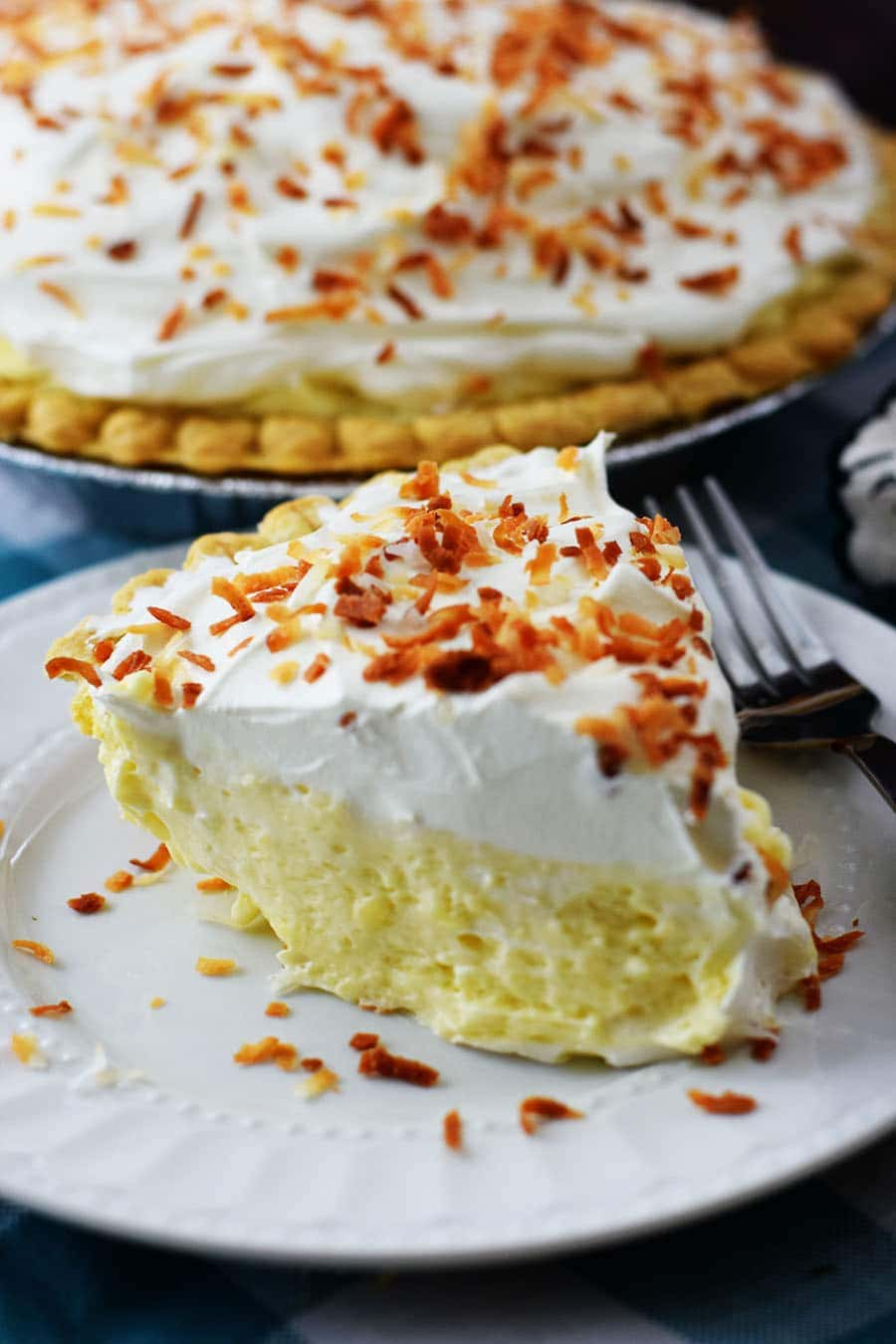 Slice of Coconut Cream Pie on White Plate with Toasted Coconut on Top