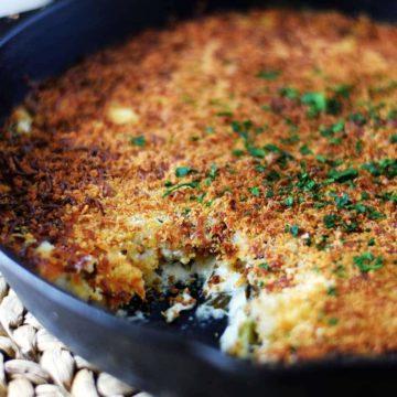 A closeup of this collard greens au gratin recipe in a black cast iron skillet