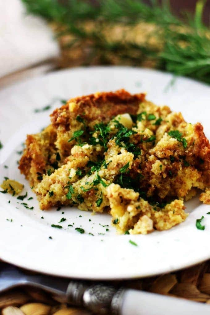 A closeup of this crock pot cornbread dressing garnished with chopped parsley on a white plate