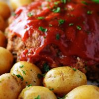 A closeup of this instant pot meatloaf with a tomato glaze and baby potatoes