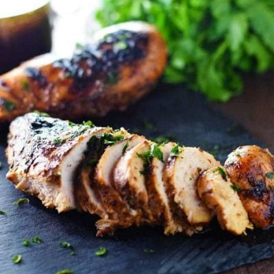Best Chicken Marinade - Grilled Chicken on a black tray with parsley.