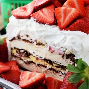 A close up of the midsection of this strawberry ice cream cake iced in whipped cream and topped with fresh strawberries