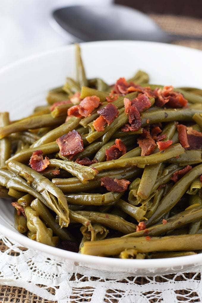 A white serving bowl filled with these southern-style green beans with crispy, crumbled bacon