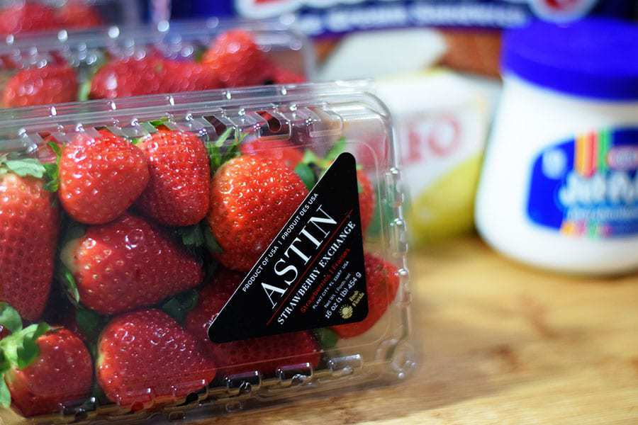 a closeup of a plastic carton of red strawberries to be used in strawberry ice cream cake