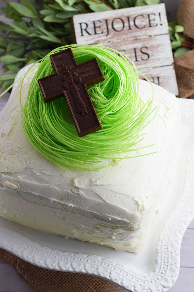 Almond Strawberry Layer Cake topped with edible green grass and a chocolate cross