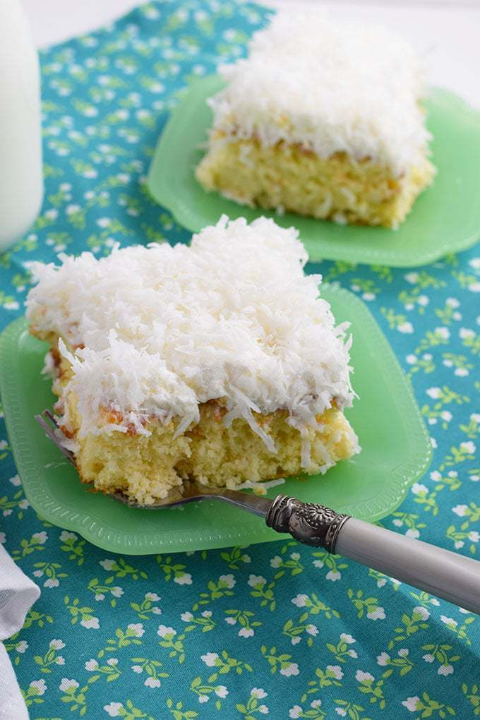 Slice of Easy Coconut Cream Poke Cake on a green plate with a fork
