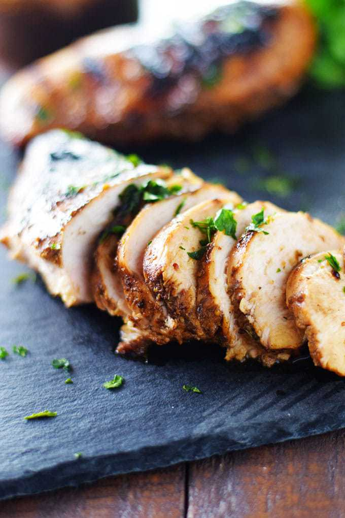 Sliced Grilled chicken on a black serving stone sprinkled with chopped parlsey