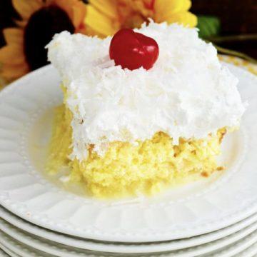 Slice of Pina Colada Poke Cake on white plate