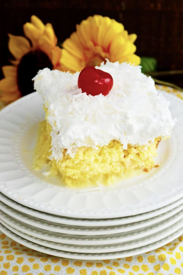 Slice of Pina Colada Poke Cake on white plate