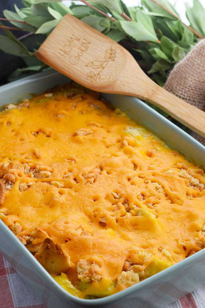 Squash Casserole in green baking dish with wooden serving spatula