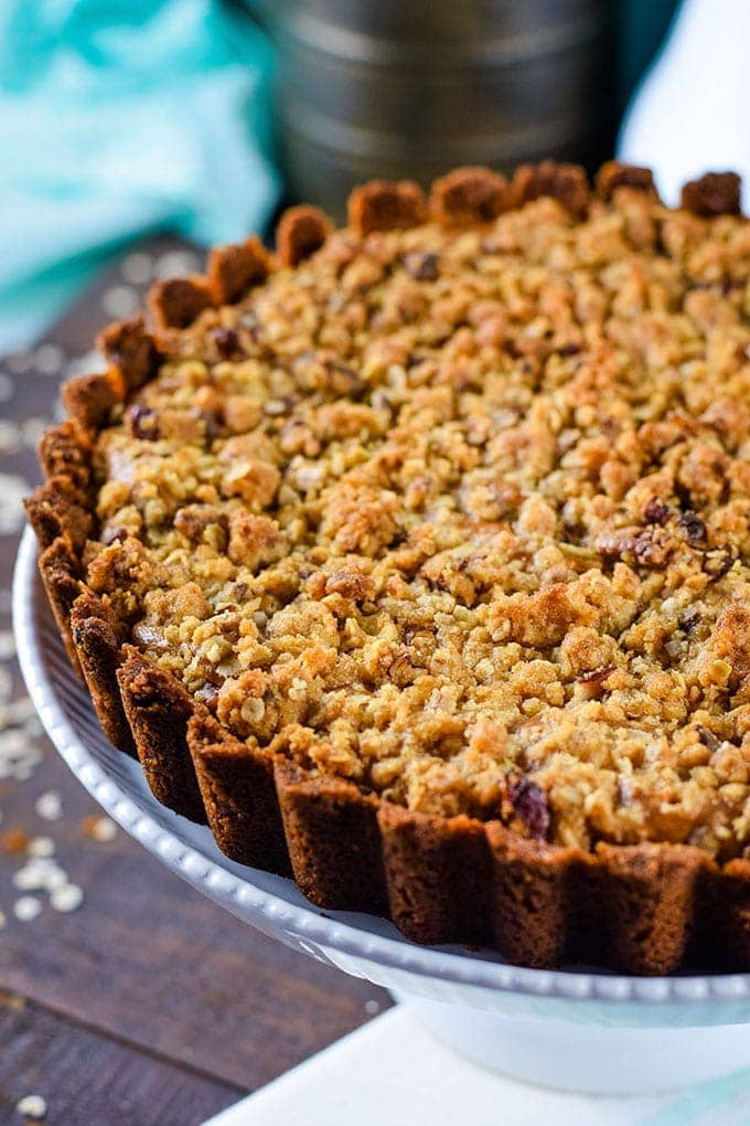 a close up of this apple butter cheesecake tart with a streusel topping on a cake stand for serving