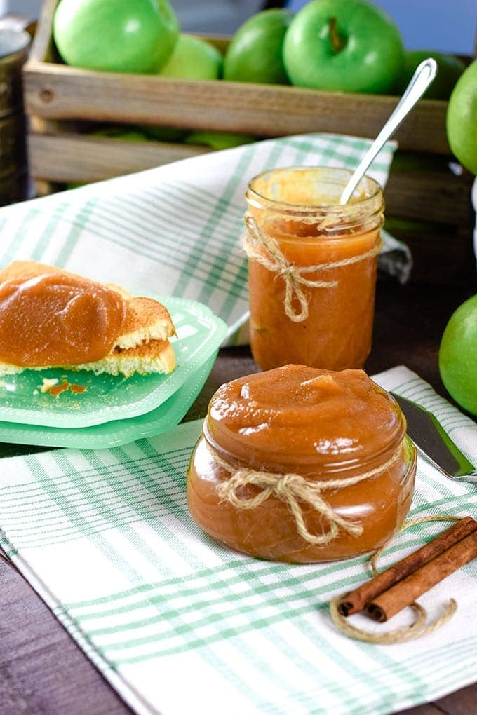 A picnic-style table with jars of this instant pot apple butter and slices of toast