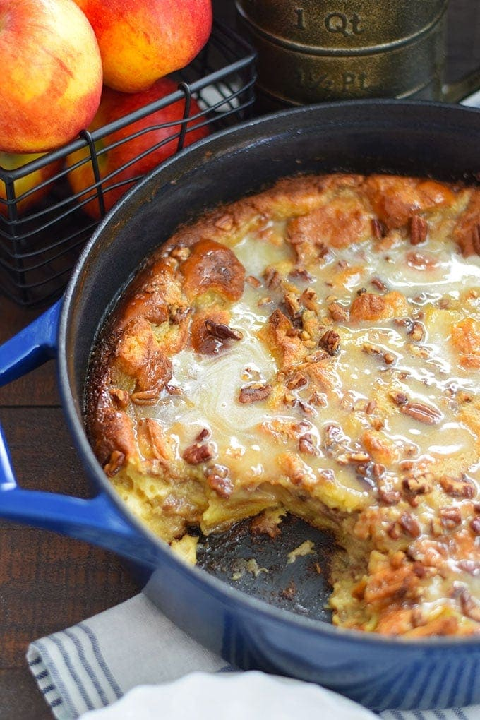 A pot of this bourbon apple pecan bread pudding recipe with a slice missing