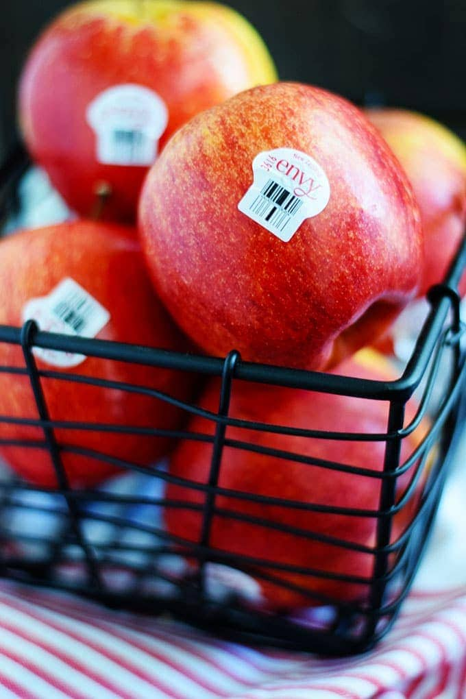 A close up of a basket of red envy apples