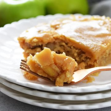 A closeup of this fresh apple cake with a brown sugar glaze on a white plate with a fork