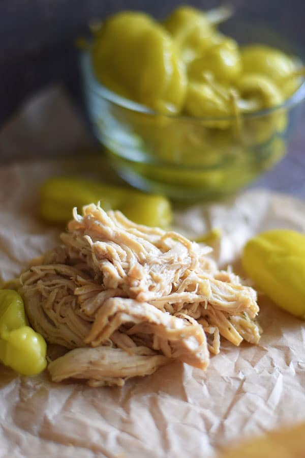 Shredded Crock Pot Mississippi Chicken on parchment paper with pepperoncinis
