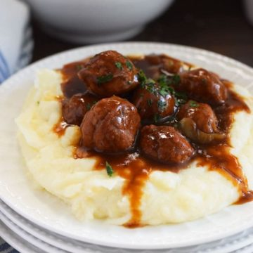 A white plate filled with mashed potatoes and these instant pot meatballs and gravy