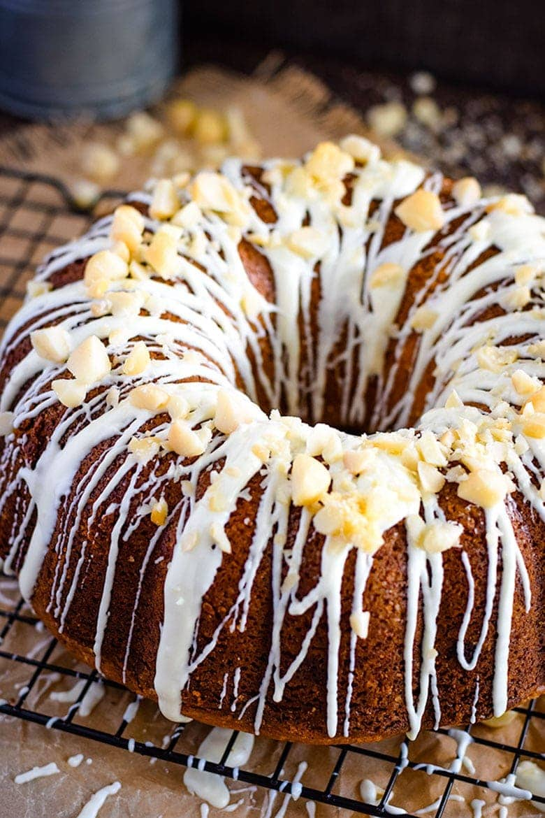 White Chocolate Macadamia Nut Pound Cake on Baking Rack with Icing and Nuts on Top
