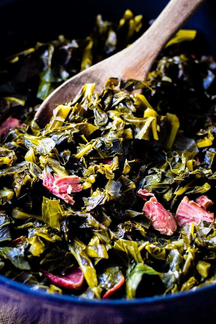 Pot of Southern Collard greens with a wooden spoon scooped full of greens.