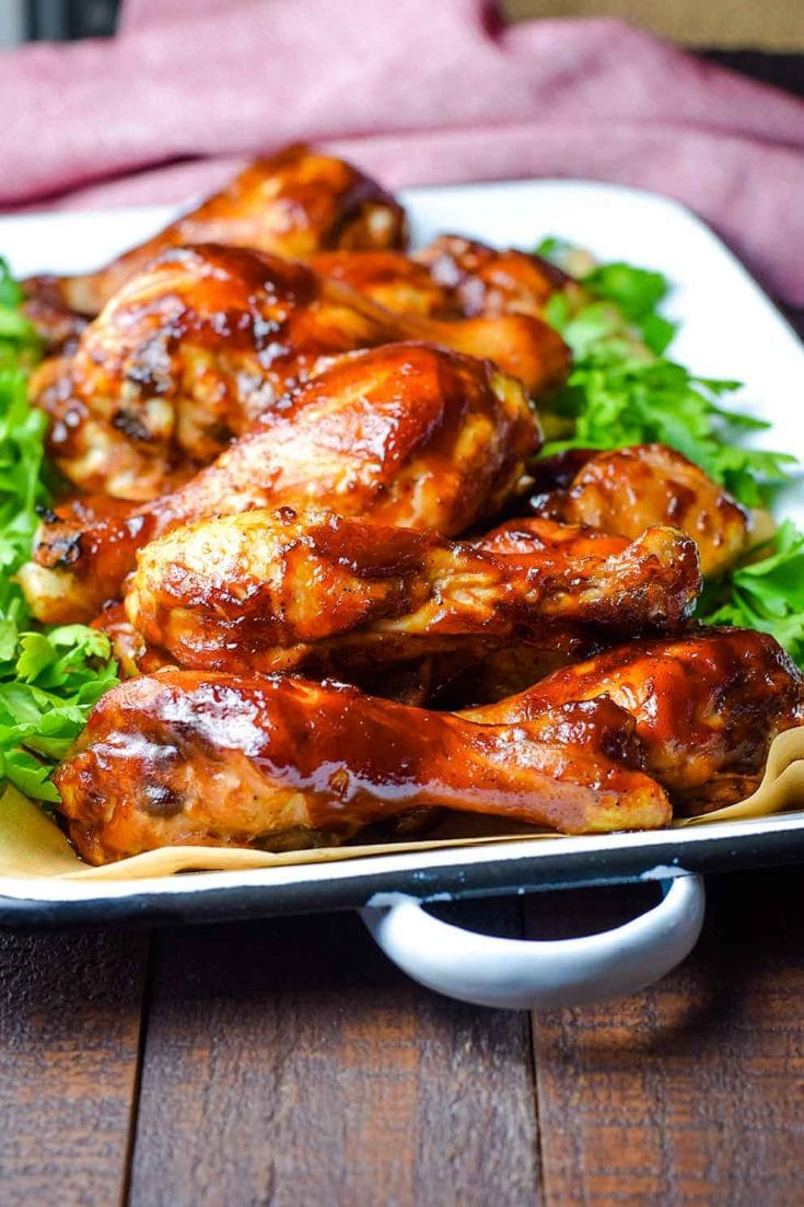 A serving dish filled with these oven baked barbecue chicken drumsticks with parsley as a garnish