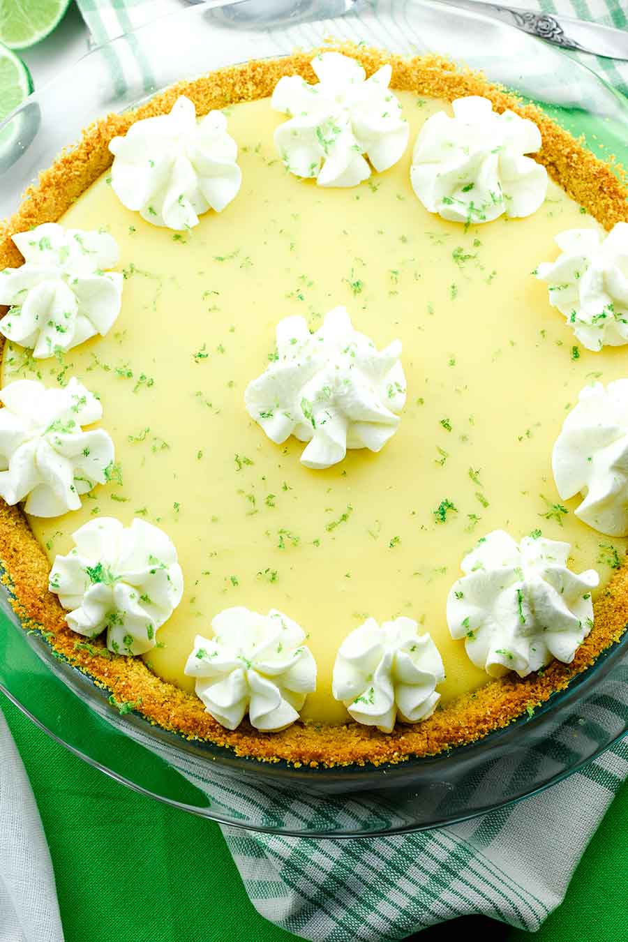 The Best Key Lime Pie topped with whipped cream and lime zest