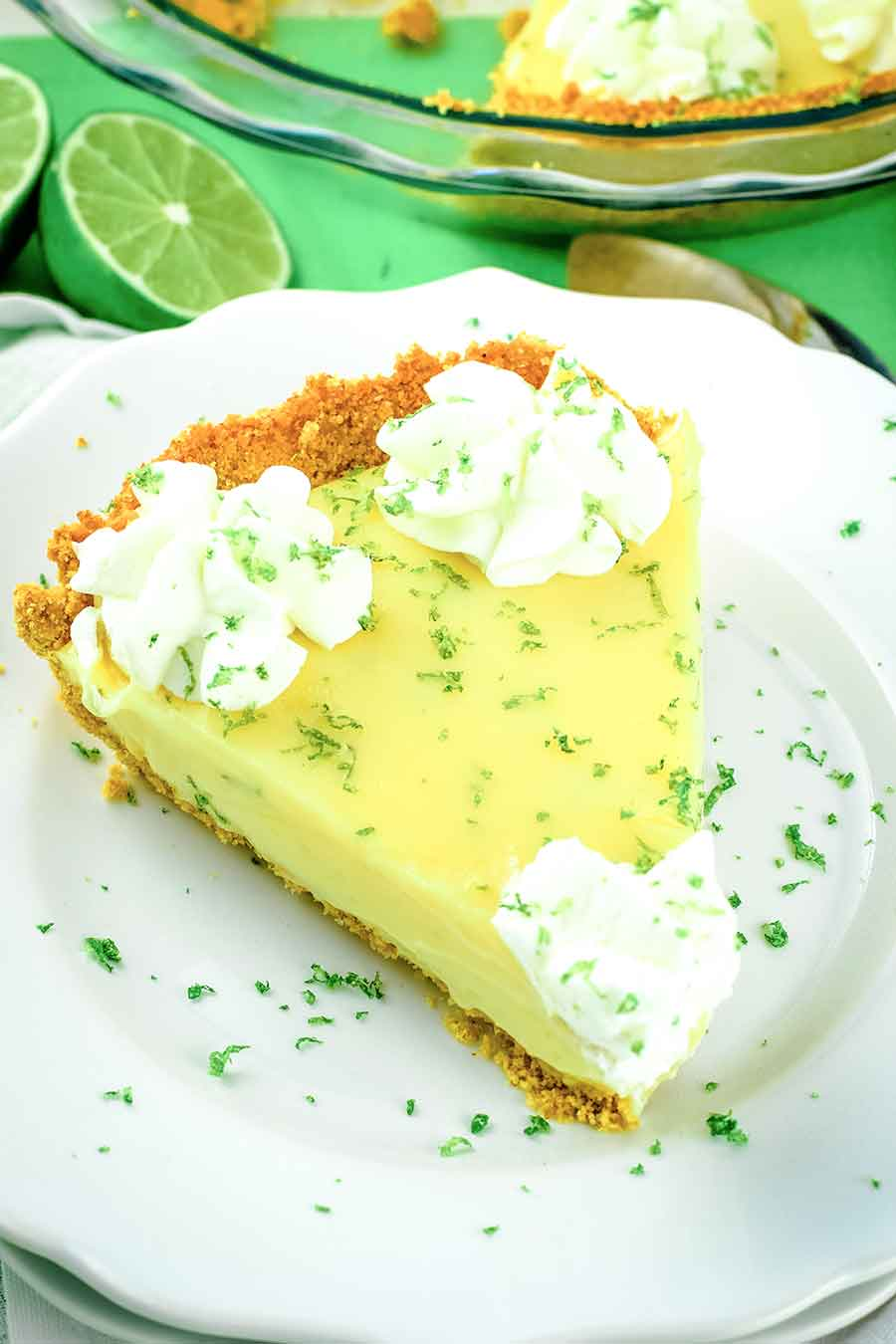 A slice of the Best Key Lime Pie topped with whipped cream and lime zest