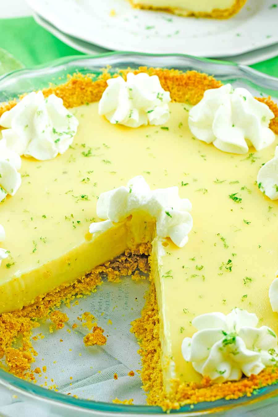 a pie dish with the best key lime pie recipe and one slice removed