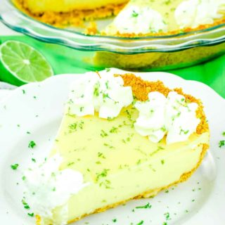 A slice of the best key lime pie on a white plate topped with whipped cream and lime zest