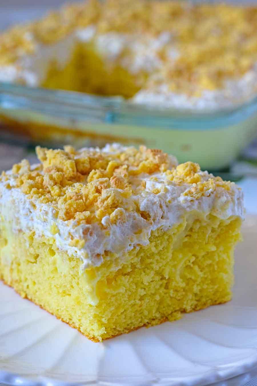 Image of a slice of lemon pudding poke cake topped with whipped lemon oreo icing.