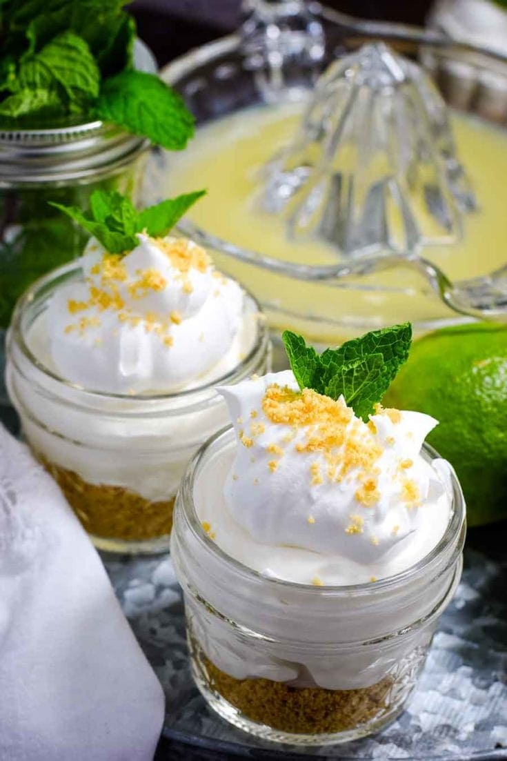 Key lime pie jars on tin cake server with lime juicer in background.