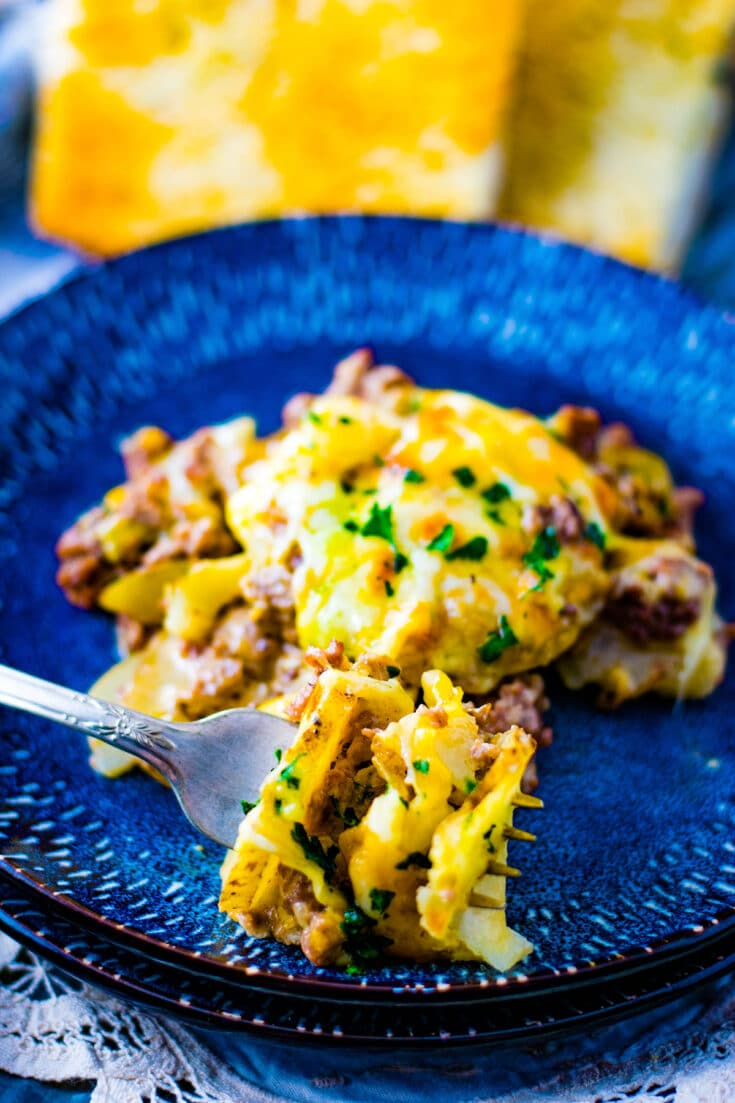 A single serving of this Easy Ground Beef and Potatoes Skillet on a dark blue plate with a fork