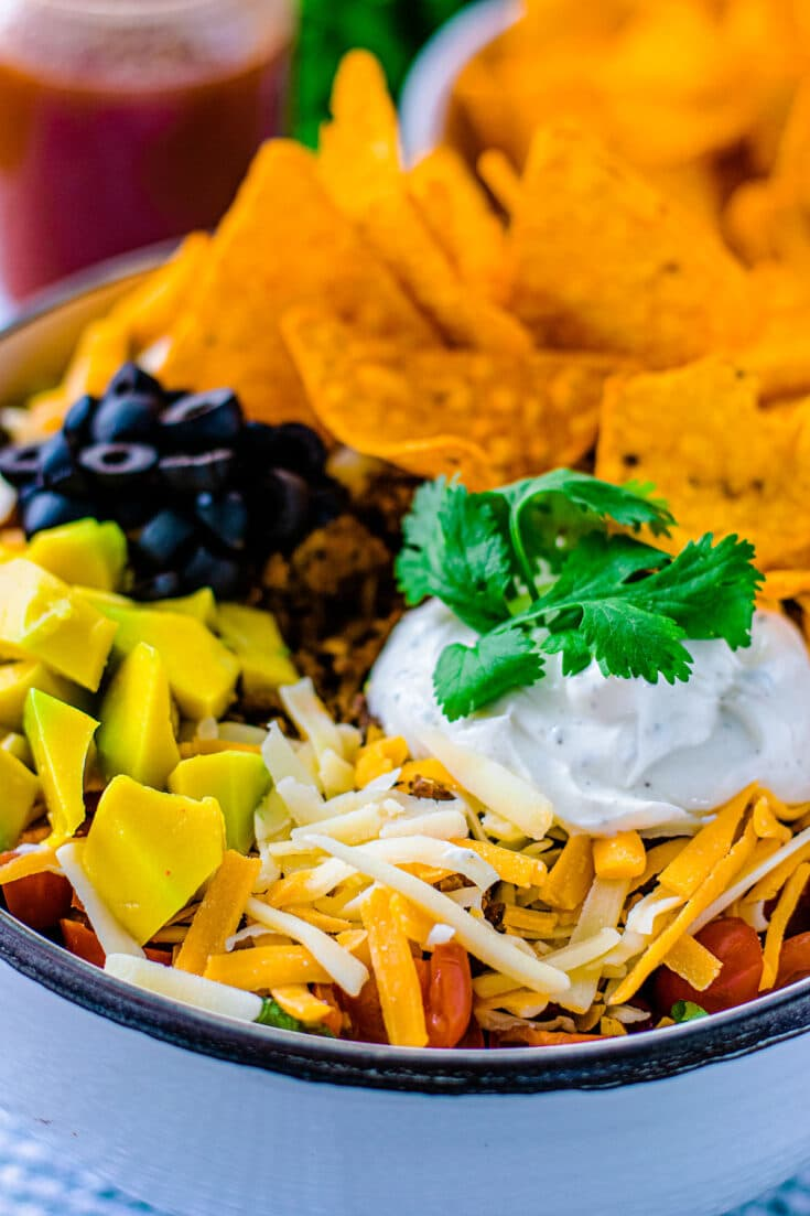 tossed green salad with seasoned ground beef, beens, cheese, lettuce, crumbled nacho chips combined to create a Dorito Taco Salad Recipe