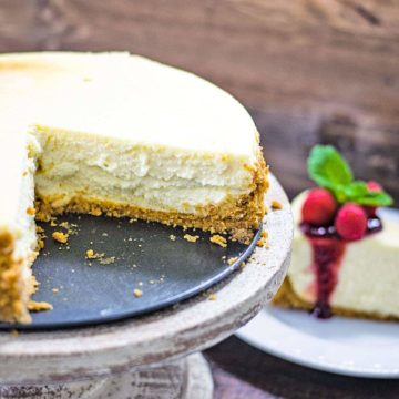 A cut cheesecake on a cake pedestal with a slice of cheese topped with raspberry sauce in the background.