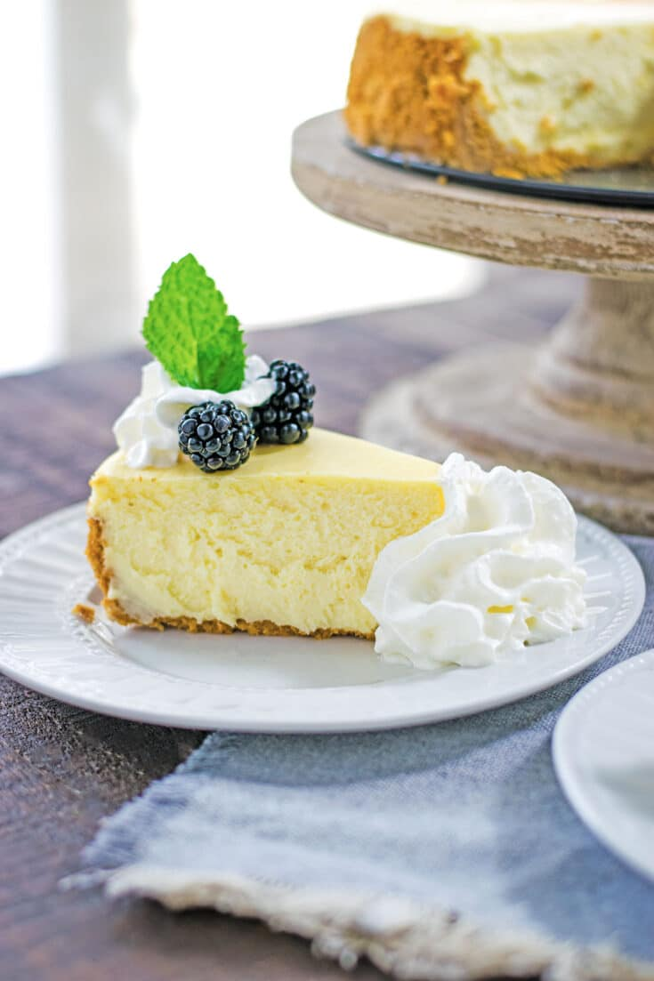 Classic Cheesecake Recipe - sliced with blackberries and whipped cream.