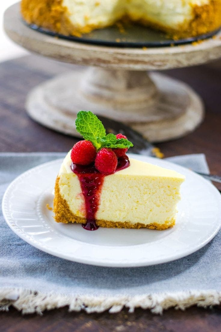 Classic Cheesecake Recipe - sliced with raspberry sauce.
