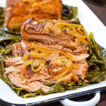 A plate of pulled pork on top of collard greens.