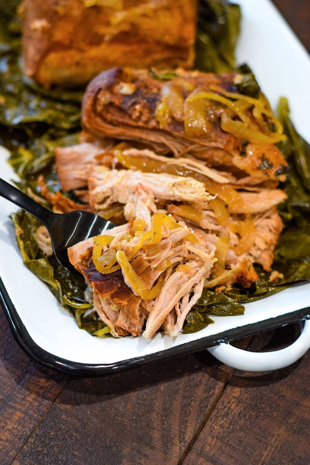 Collard Green Wrapped Pork Roast on white serving tray
