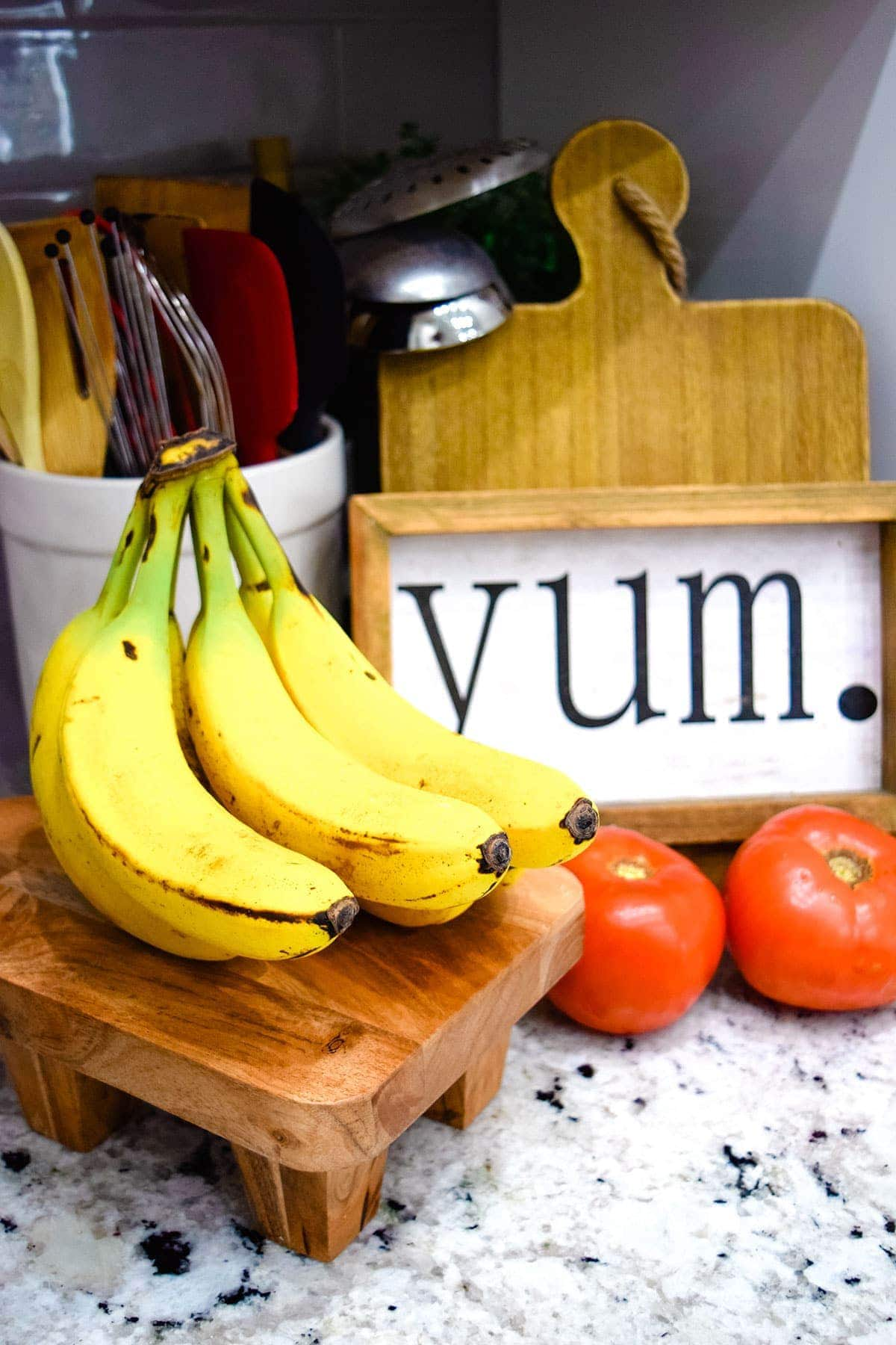Bananas on kitchen counter with tomatoes and yum kitchen sign
