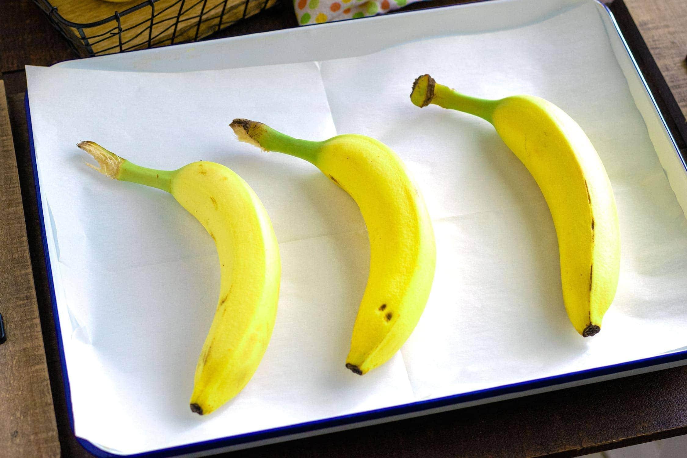 Three yellow bananas on a baking sheet