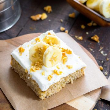 A slice of banana cake on a plate, with sliced bananas and nuts on top.