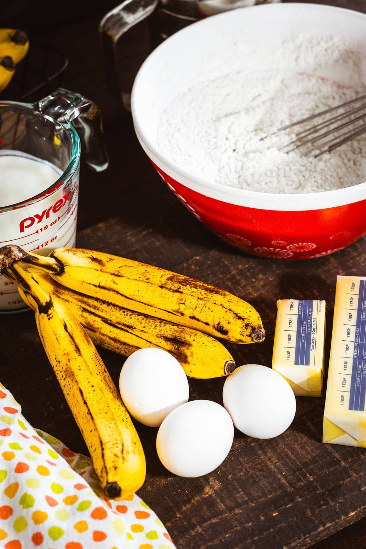 Ingredients for Banana Cake. Ripe bananas, eggs, butter, flour mixture in a red bowl and a measuring cup of buttermilk.